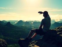 Man sit on peak of rock. Hiker shadowing eyes with raised arm Stock Image