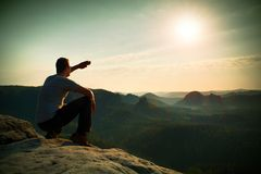 Man sit on rock edge. Hiker makes shadow with hand and watch to colorful mist in forest valley. Stock Images