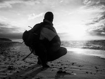 MAn sit at sea. Man sit at evening sea. Hiker with backpack sit in squatting possition  along beach. Vintage Style Toned effect Stock Photos