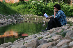 Man sit on stone river. Man sit on stone in a river in summer Stock Photography