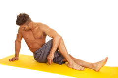 Man sit stretch twist look down Royalty Free Stock Photos