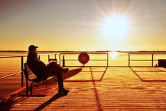 Man sit on wharf and enjoy morning at sea. Sunny clear blue sky, smooth water level Royalty Free Stock Images