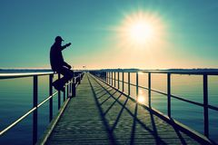 Man sit on wharf and enjoy morning at sea. Sunny clear blue sky, smooth water level Stock Photos