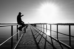 Man sit on wharf and enjoy morning at sea. Sunny clear blue sky, smooth water level Stock Photography
