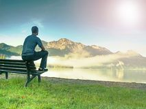 Man sit on wooden bench at coast of lake bellow blue mountains stock image
