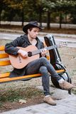 Man on bench. Man siting on bench in park with guitar stock photo