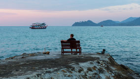 A  man sits alone on a bench on the seafront promenade. Royalty Free Stock Photos