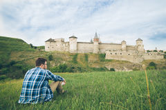 Man sits alone in front of old castle Royalty Free Stock Images