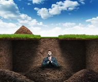 Man sits as hostage underground. Businessman sits as hostage underground in the soil Stock Images