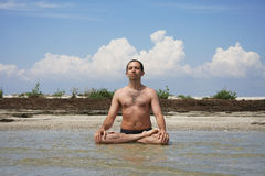 A man sits ashore sea in the pose of lotus Stock Images