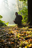 Man sits in the autumn forest Stock Images