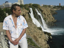 A man sits on a background düden waterfalls in Antalya Royalty Free Stock Images