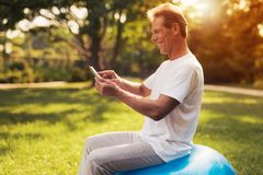 A man sits on a ball for yoga and looks at something on his tablet. He smiles. A man sits in a park on a blue bowl for yoga. He is looking at something on his Stock Image