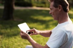 A man sits on a ball for yoga and looks at something on his tablet. He smiles. A man sits in a park on a blue bowl for yoga. He is looking at something on his Stock Photography