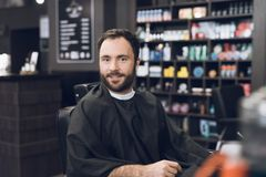A man sits in a barber`s chair in a man`s barbershop, where he came to cut his hair. A man came to the salon to get a haircut. While he waits for the stock images