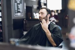 A man sits in a barber`s chair in a man`s barbershop, where he came to cut his hair. A man came to the salon to get a haircut. While he waits for the stock photos