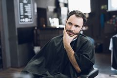 A man sits in a barber`s chair in a man`s barbershop, where he came to cut his hair. A man came to the salon to get a haircut. While he waits for the stock photography