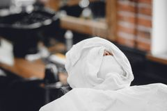 Man sits in barbershop chair and steam his face with hot towel in front of royal beard shaving razor.  royalty free stock photography