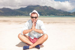Man sits on the beach and prays Royalty Free Stock Photo