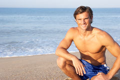 Man sits on beach relaxing Stock Photography