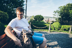 Man sits on a bech in warm summer evening. Looking on city view Royalty Free Stock Images
