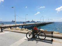 A man sits on a bench behind a bicycle gazes towards the sea at Molos promenade in Limassol, Cyprus royalty free stock photos