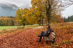 Man sits on a bench and looks at surrounding autumn Royalty Free Stock Images