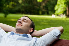Man sits on bench Stock Photography