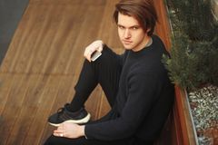 A man sits on a bench with a phone. Fashion man looks into the distance. Fashion man outside in sweater. royalty free stock photos