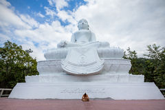 Man sits beneath white buddha statue. Phra That Maeyen temple, Thailand Royalty Free Stock Image