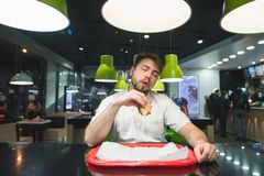 A man sits in bisro with burger in his hands and enjoys the taste of delicious food. A man likes delicious fast food. Fasc food restaurant Stock Image