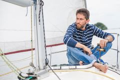 Man sits on bow of sailing yacht and holds binoculars Stock Photo