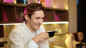Man sits in a cafe laughs smiles happy holds a black cup of coffee in his hand drinks Communicates stock video