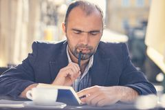 Man sits in a cafe and notes in a notebook. Attractive man sits in a cafe and notes in a notebook Royalty Free Stock Images