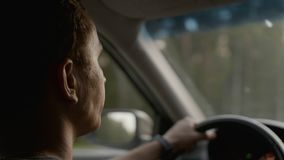 Man sits in the car and looks ahead to the road