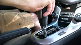 The man switches the selector of the automatic transmission to drive mode. The man sits in the car and switches the selector of the automatic transmission to stock video footage