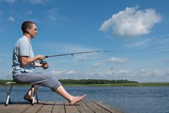 A man sits on a chair on the beach and catches a fish stock photos