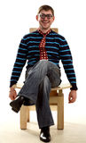 Man sits on the chair in funny glasses and tie Royalty Free Stock Image