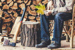 Man sits in chair, next to tree stump and ax Stock Photography