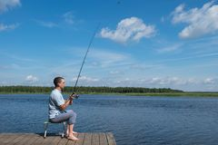 A man sits in a chair on the pier and catches fish on the lake, active recreation stock images