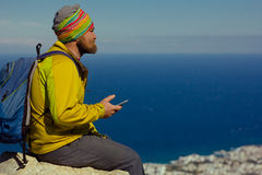 Man sits on a cliff above the sea with a smartphone in hand Stock Image