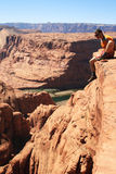 Man sits cliff edge. A man sits on the edge of a sandstone cliff overlooking Glen Canyon, Arizona Stock Image