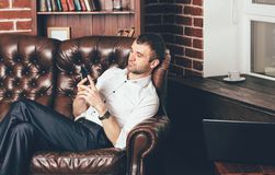 A man sits on a comfortable leather sofa and holds the phone in his hands on the background of the stylish interior of the room. royalty free stock image