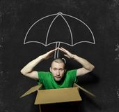 A man sits in a cramped box. On the background of the picture of the umbrella with chalk on blackboard stock image