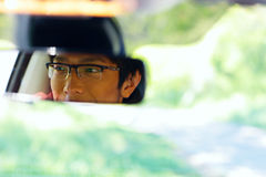 Man sits on driver's seat and Looks in the rear-view mirror Stock Photo