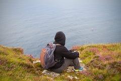Man sits on the edge of cliff enjoying sea view. Horizontal Stock Photos