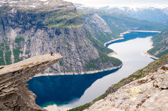 Man sits on the edge of a cliff and looks at mountain lake (Trol Stock Photo