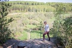 Man sits on the edge of a cliff. A man stand on the edge of a cliff and looking to the valley landscape Royalty Free Stock Images