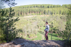 Man sits on the edge of a cliff. A man stand on the edge of a cliff and looking to the valley landscape Royalty Free Stock Image