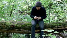 Man sits on a fallen tree in the wood and reaching for mushrooms. Guy woke up in the woods on a log. Video, 2016 stock video footage